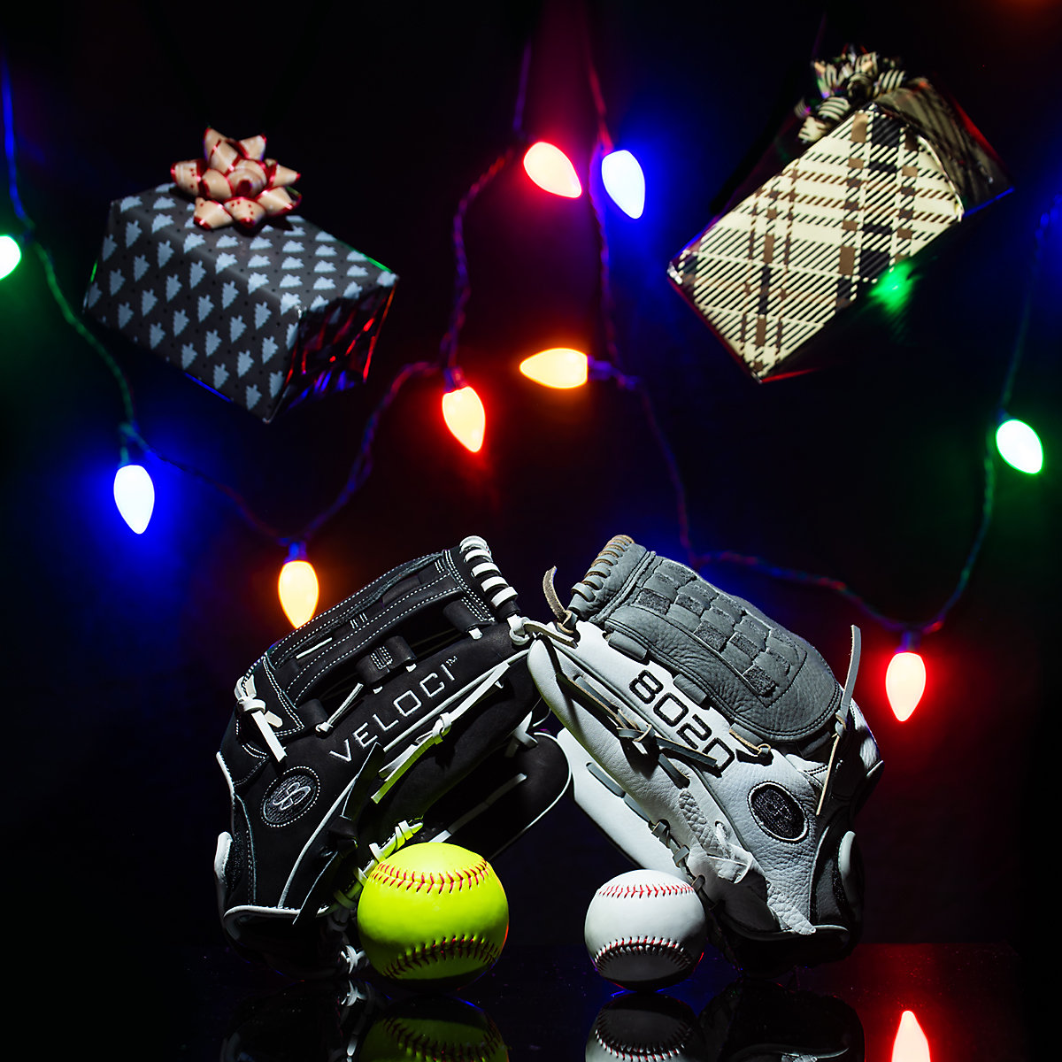 Baseball gloves and balls on display with holiday presents and lights