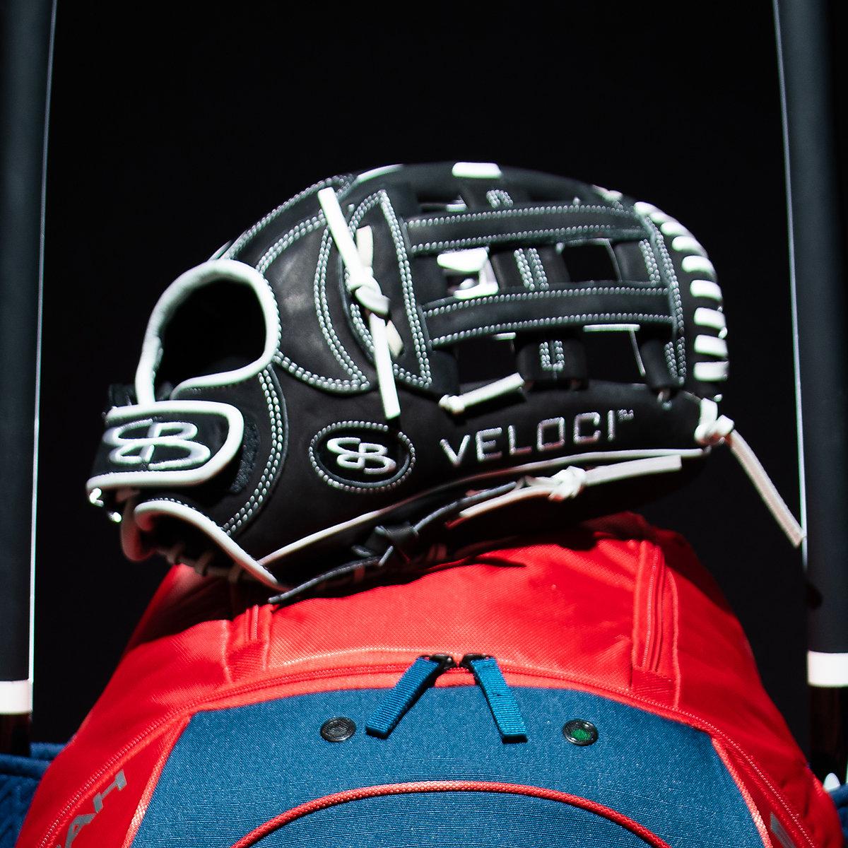 A baseball glove on top of a bat bag