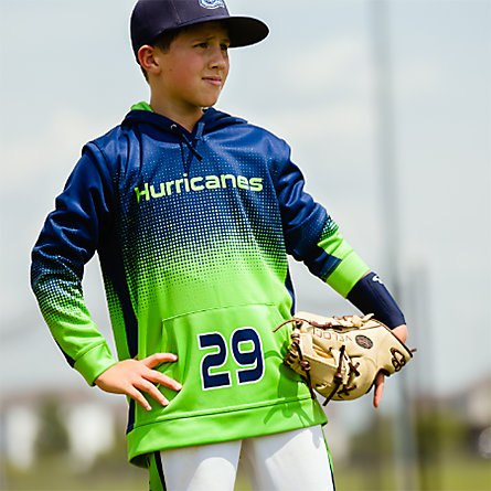 A young baseball player in a blue and green pullover