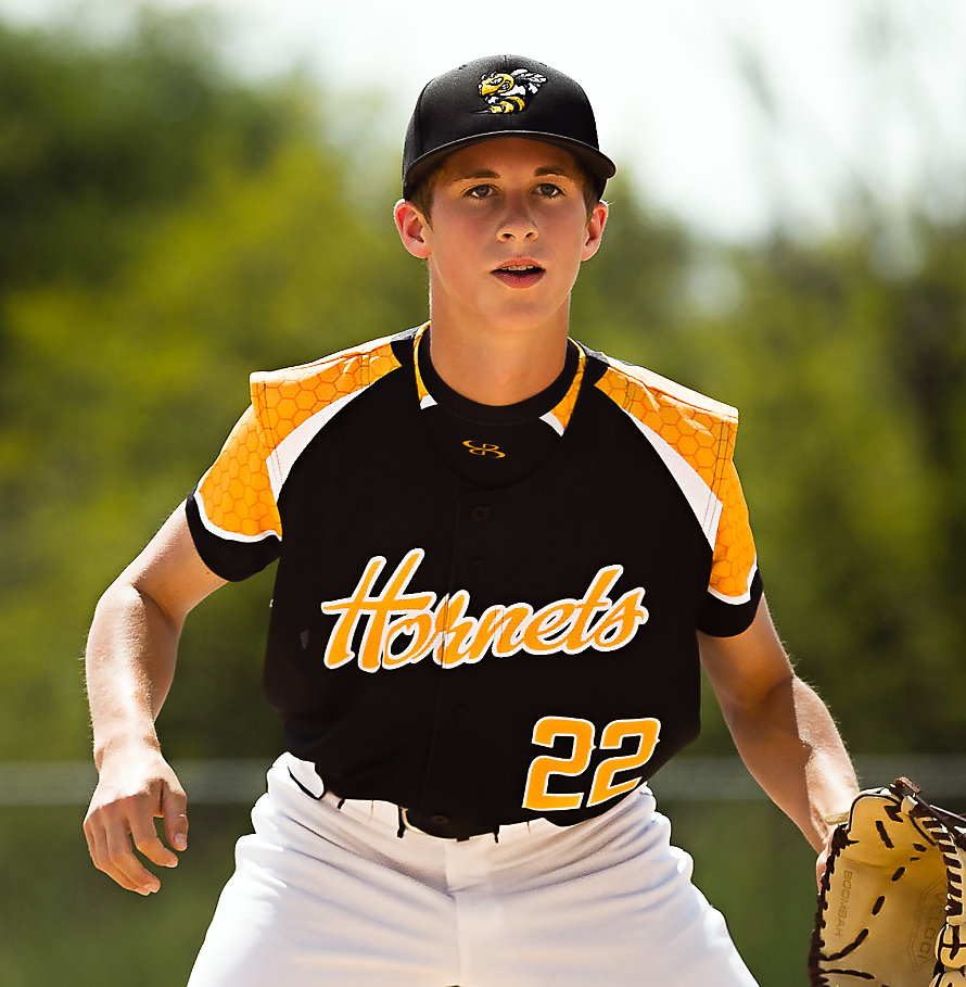 A baseball player in a black, yellow and white jersey