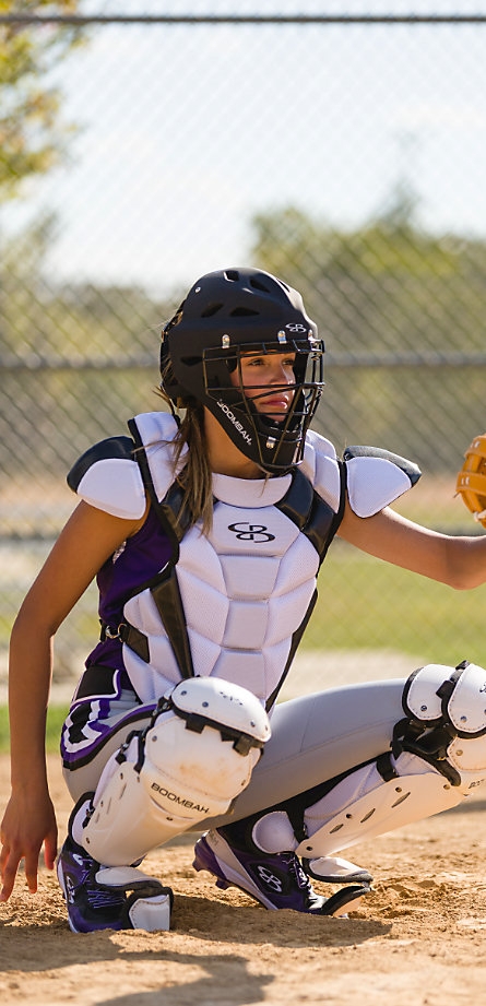 A bsoftball player in purple and white catcher's gear