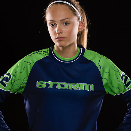 A girl in a green and blue softball jersey