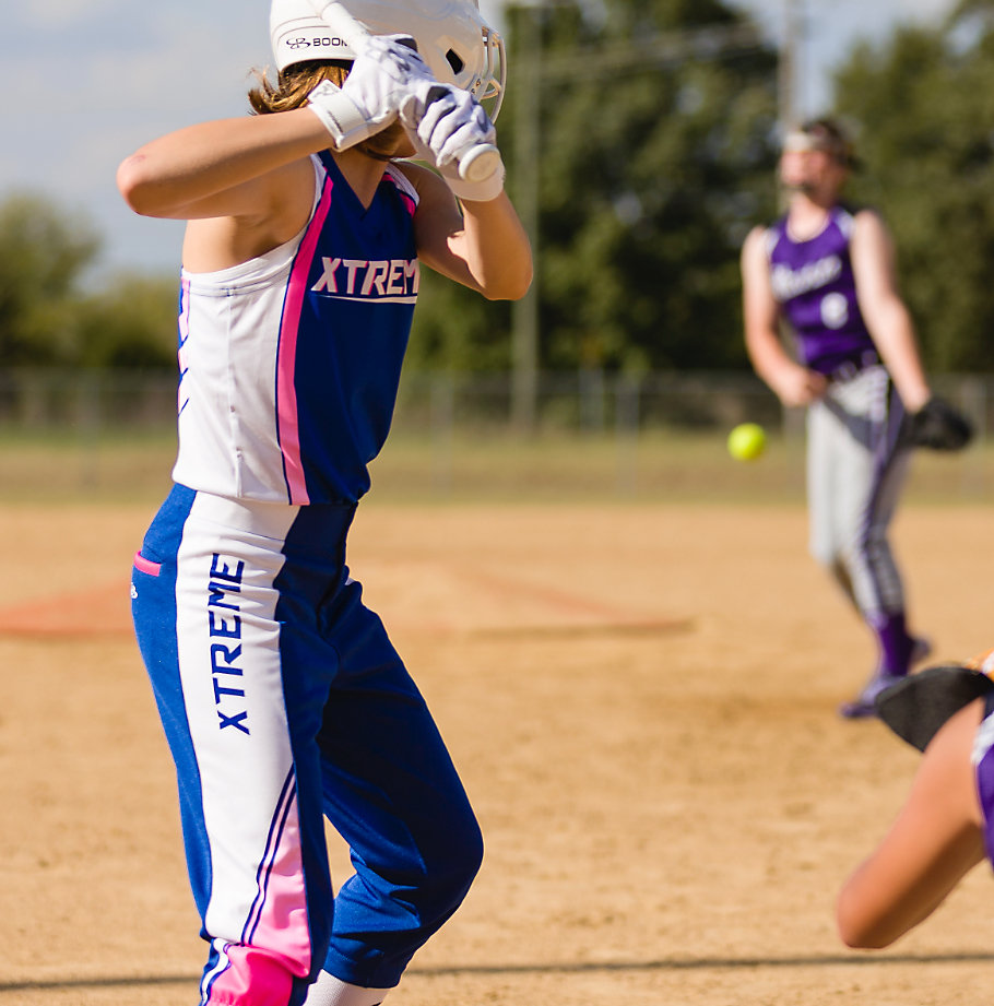 A softball player at bat in a blue, pink and white jersey