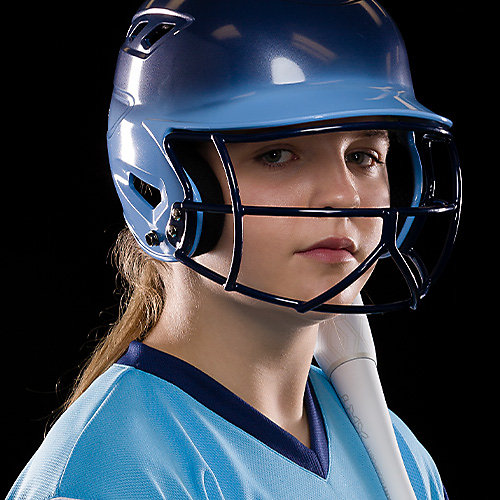 A girl wearing a dark blue and light blue helmet with softball face mask