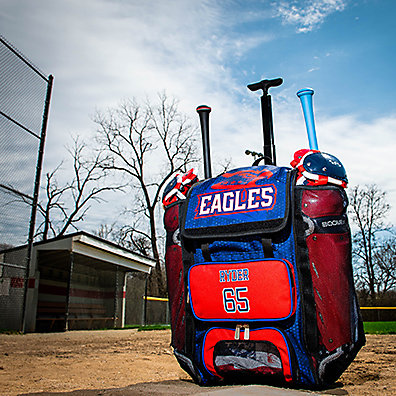 A blue and red custom bat bag filled with baseball gear