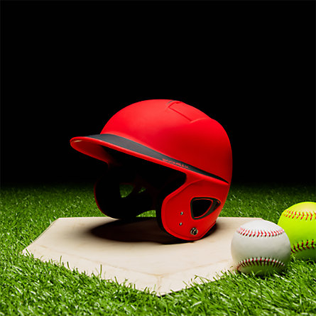 A red batting helmet on a plate next to two baseballs