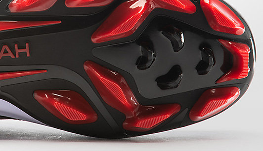 The red and black sole of baseball shoe with molded cleats