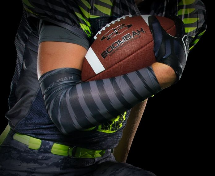 Football player holding ball with grey and black arm sleeve
