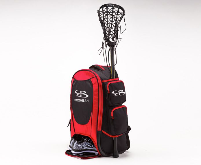 Red and black branded gear bag holding shoes and lacrosse stick