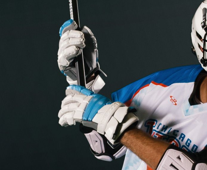 Male lacrosse player with white and blue gloves
