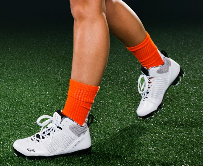 White women's cleats with orange socks
