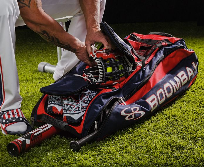 Red and navy Beast bag with baseball equipment being put inside
